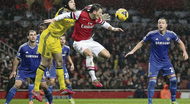 Chelsea goalkeeper Petr Cech punches the ball off the head of Arsenal's Mesut Ozil GETTY