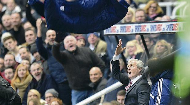 Stoke City manager Mark Hughes throws his coat in the air in frustration after his team had two men sent off in the defeat to Newcastle