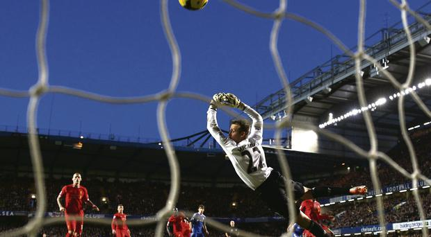Liverpool goalkeeper Simon Mignolet dives in vain as Eden Hazard fires the equalising goal at Stamford Bridge yesterday Julian Finney/Getty Images