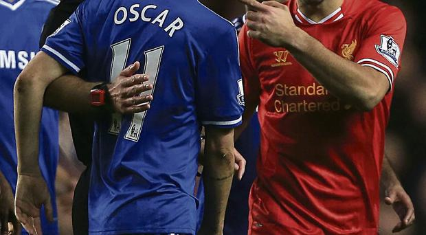 Luis Suarez argues with referee Howard Webb and Chelsea player Oscar after an incident late in the game at Stamford Bridge