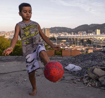 A young boy plays football in the Mangueira shantytown, which is located close to the famed Maracana Stadium
