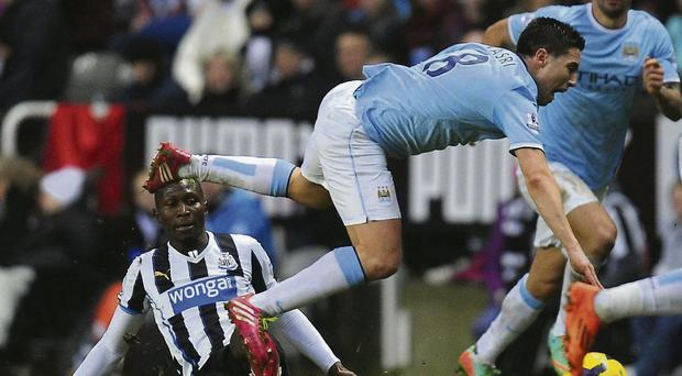 Newcastle player Mapou Yanga-Mbiwa fouls Samir Nasri who was later stretchered off
