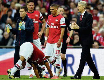 Arsene Wenger speaks to his weary players before extra-time of their semi-final victory over Wigan