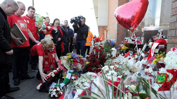 Family members of Keith McGrath lay flowers at the Hillsborough memorial at Anfield.
