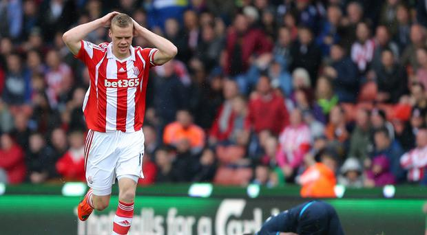 Ryan Shawcross, left, holds his head after fouling Danny Rose, right