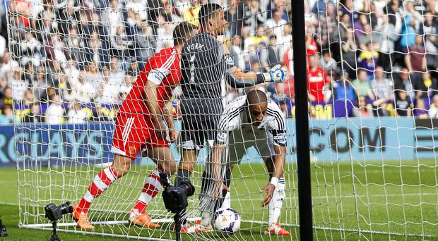 Ashley Williams picks the ball out of the net after Rickie Lambert, left, scored Southampton's winner