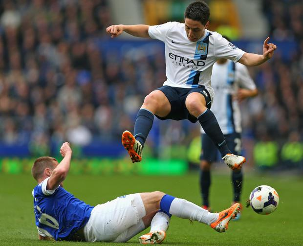 Samir Nasri of Manchester City hurdles the tackle of James McCarthy during yesterday's Premier League match at Goodison Park