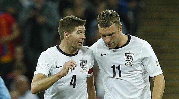England's Rickie Lambert celebrates scoring his teams second goal of the game against Moldova with teammate Steven Gerrard