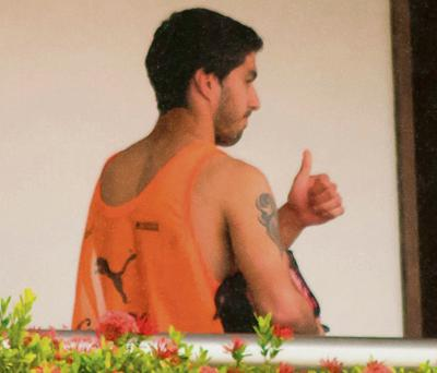 Uruguay's Luis Suarez is seen embracing a member of the coaching staff on a balcony at the team's hotel in Natal on the day as the striker was hit with the biggest ever World Cup ban for biting Italy's Giorgo Chiellini