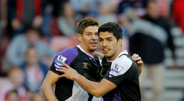 Luis Suarez, right, has been hailed as outstanding, not least by Liverpool skipper Steven Gerrard, left