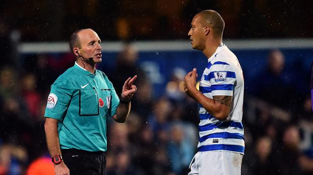 Referee Mike Dean, left, was surrounded by QPR player's during their match with Manchester City at Loftus Road