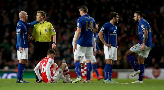 Aaron Ramsey sits injured on the ground during Arsenal's win over Leicester