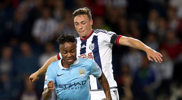 Raheem Sterling (left) gets away from West Brom's James Chester on his Manchester City debut.