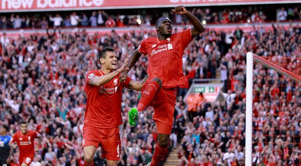Christian Benteke, right, celebrates his first Liverpool goal in front of the Kop