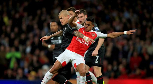 Arsenal's Alexis Sanchez (right) and Liverpool's Martin Skrtel battle for the ball