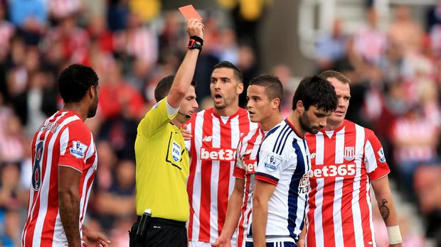 Michael Oliver shows his first red of the game to Stoke's Ibrahim Afellay, third from right