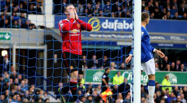 Wayne Rooney tempers his celebration after scoring at Everton