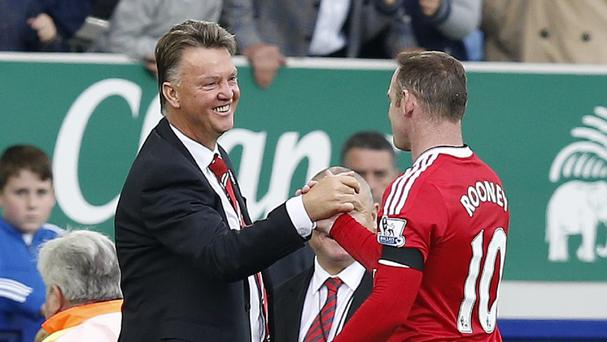 Manchester United manager Louis van Gaal celebrates with Wayne Rooney, who scored the third goal against Everton