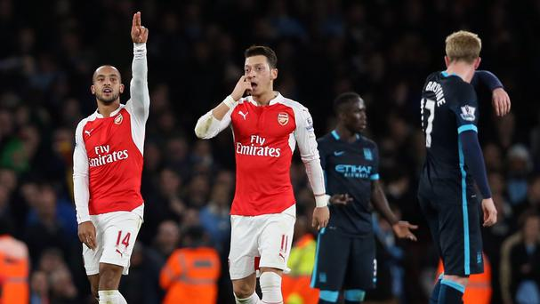 Mesut Ozil, pictured centre, fought off a chest infection to guide Arsenal to a win over Manchester City