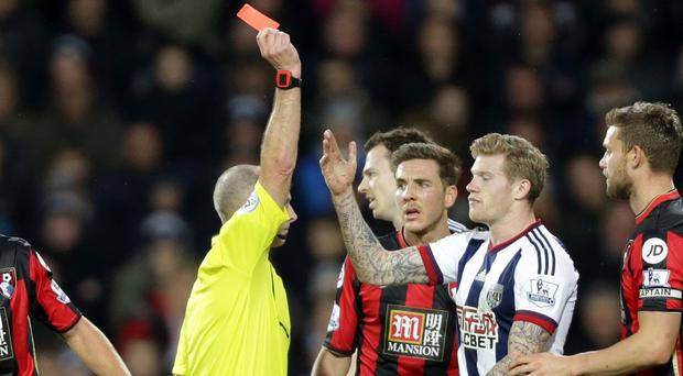 West Brom's James McClean, right, is shown a red card by referee Mike Dean after his tackle on Adam Smith