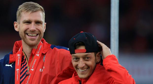 Arsenal's Per Mertesacker towers over Mesut Ozil, with the pair lauded as key dressing-room influences by Arsene Wenger