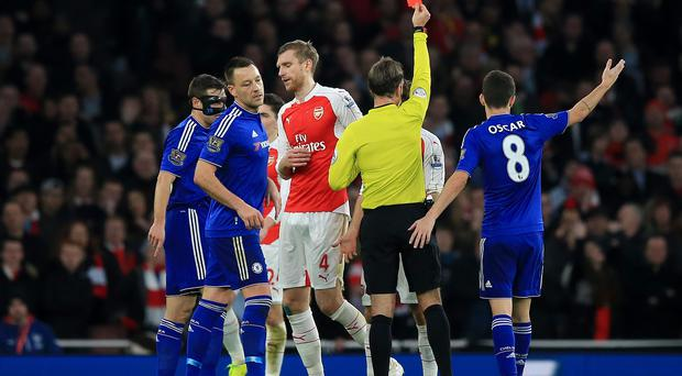 Arsenal's Per Mertesacker is shown a red card by referee Mark Clattenburg