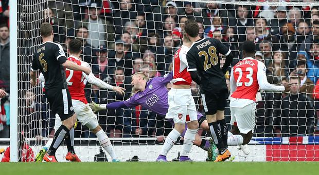 Arsenal's Danny Welbeck, right, looks on as his late header beats Kasper Schmeichel