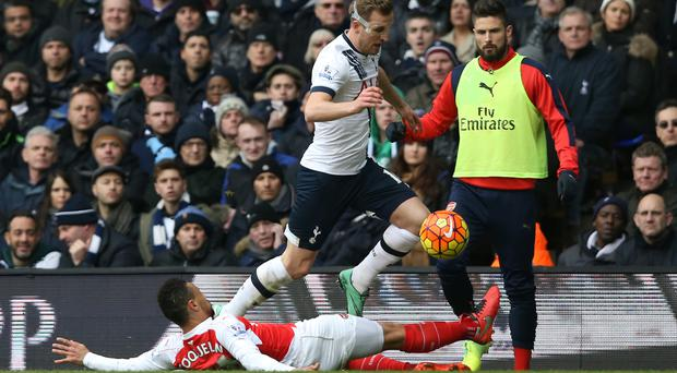 Francis Coquelin, sliding, saw red after this challenge on Harry Kane