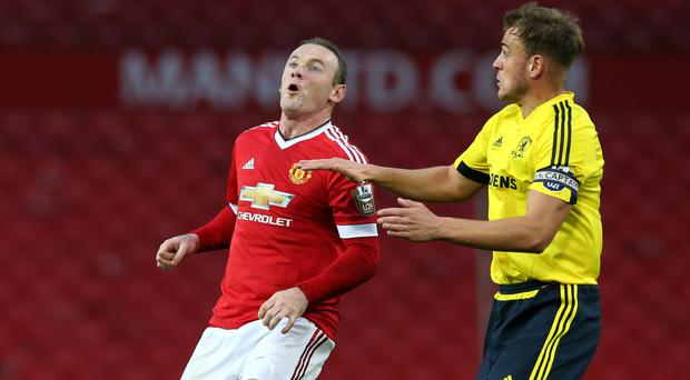 Wayne Rooney, left, challenges for the ball in his comeback appearance