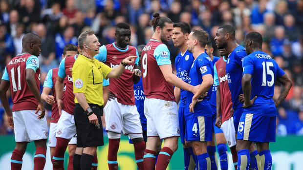 Referee Jonathan Moss awarded a penalty to after a foul by Andy Carroll, centre, on Jeff Schlupp, far right