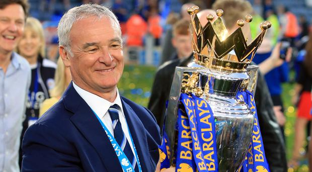 Leicester manager Claudio Ranieri proudly holds the Premier League trophy