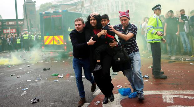 A woman and child are helped past West Ham fans in the chaos before kick-off last night. Photo: Getty