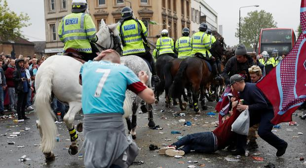 A West Ham fan lies on the ground as fans clash with police outside the stadium before the match. Photo: PA