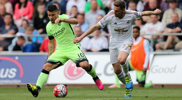 Sergio Aguero, left, battles for the ball during Manchester City's 1-1 draw at Swansea, which all-but secured their place in next season's Champions League