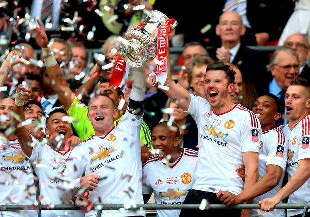 Wayne Rooney and Michael Carrick lift the FA Cup following yesterday's extra time victory. Photo: PA