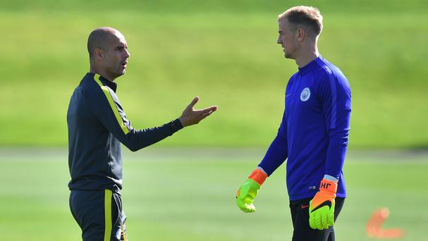 Manchester City manager Pep Guardiola, left, spoke to goalkeeper Joe Hart during training in the summer