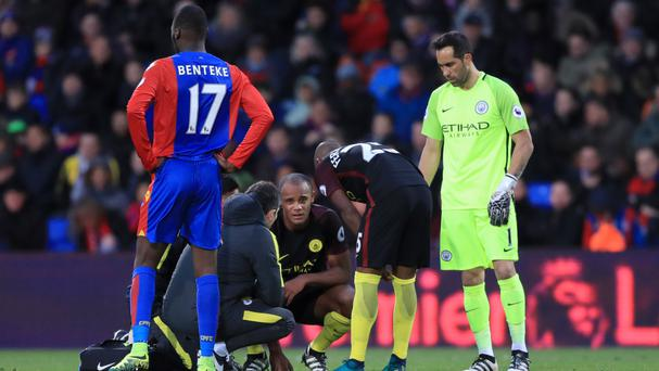 Vincent Kompany, crouched, suffered a knee injury in his accidental collision with Claudio Bravo