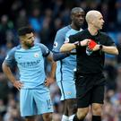 Match referee Anthony Taylor (right) puts his red card away after sending-off Manchester City's Sergio Aguero (left) during the Premier League match at the Etihad Stadium, Manchester.