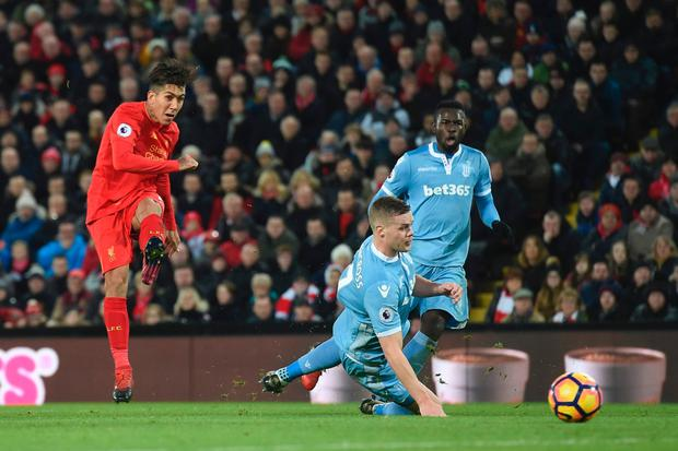 Roberto Firmino scores Liverpool's second goal against Stoke City last night. Photo: Getty