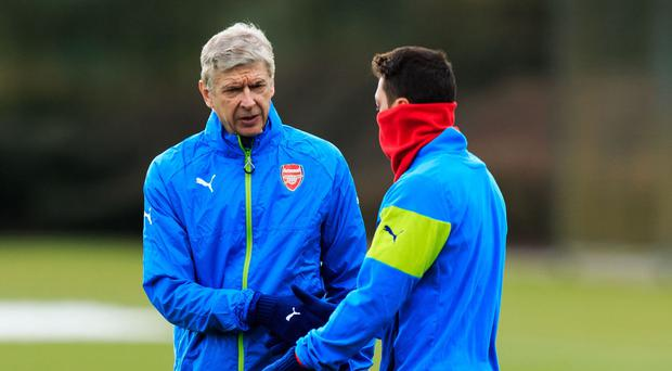 Mesut Ozil, pictured right, says he wants clarity over the future of Arsenal boss Arsene Wenger before committing himself