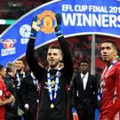 Chris Smalling, right, celebrates United's cup win alongside David De Gea
