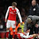 Arsenal manager Arsene Wenger helps up Alexis Sanchez after a throw-in incident during the match against Leicester
