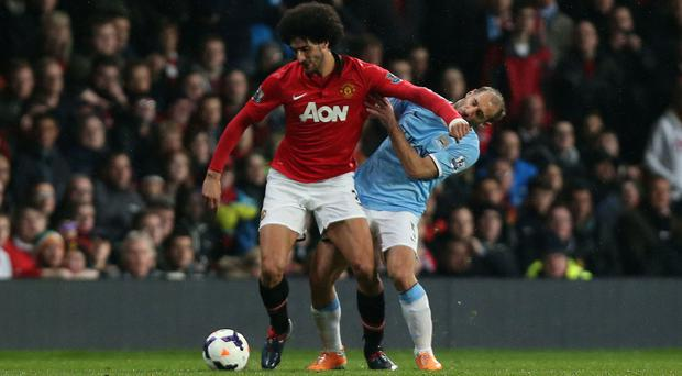 Marouane Fellaini (left) tussles with Pablo Zabaleta (right) before being sent off late on in a 0-0 draw in the Manchester derby
