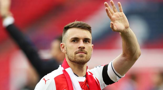 Aaron Ramsey, pictured, is delighted that Arsene Wenger will be in charge at Arsenal next season