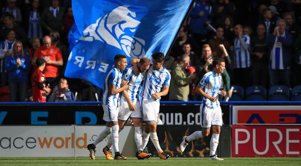 Huddersfield's Laurent Depoitre, second left, celebrates with his team-mates after scoring against Leicester