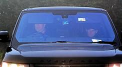 Wayne Rooney (right) is driven in to Everton's Finch Farm training ground after being banned from driving for two years