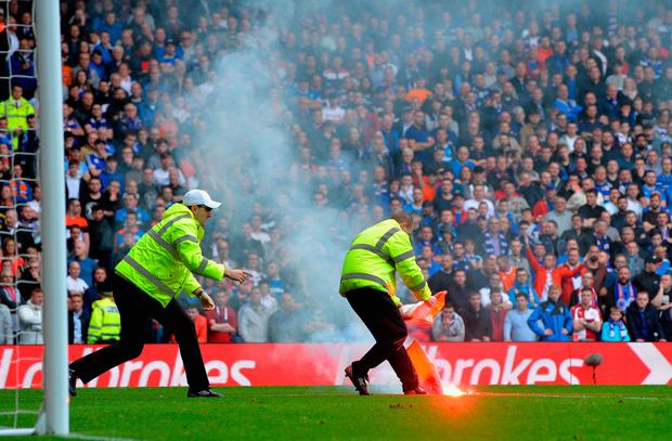 Stewards take care of a flare that was thrown onto the pitch at Ibrox yesterday. Photo: Getty