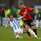 Huddersfield's Tom Ince puts in a challenge on Manchester United's Henrikh Mkhitaryan at John Smith's Stadium Photo: Reuters