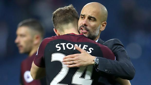 John Stones and Pep Guardiola embrace after the final whistle of a recent Premier League game at West Brom