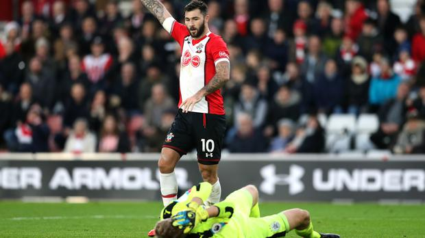 Charlie Austin signals while Huddersfield goalkeeper Jonas Lossl lies injured